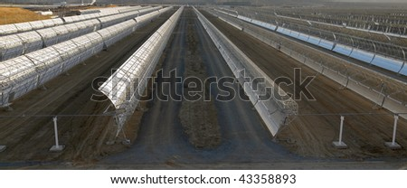 panoramic view of solar parabolic mirrors for producing solar power - stock photo