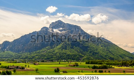 Panoramic view of the Alps from the window of one of the many castles of Austria (Hellbrunn). At the foot of the mountains, wide Alpine fields and many farm houses with agricultural machinery, Austria