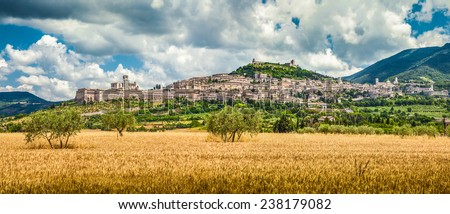 Panoramic view of the ancient town of Assisi with dramatic cloudscape and golden harvest fields, Umbria, Italy - stock photo
