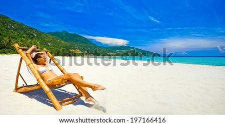 Panoramic view of the beach with an attractive woman sunbathing alone. - stock photo