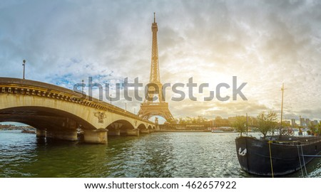 Panoramic view of the Eiffel Tower and Jena bridge from the river Seine embankment, Paris, France. Autumn. Beautiful sitycape in backlit morning sunbeam.