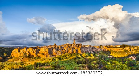 Panoramic view of the medieval town of Pitigliano with dramatic cloudscape at sunset, Tuscany, Italy - stock photo