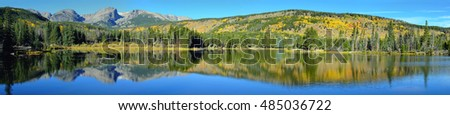 panoramic view of the mountains and alpine lake with reflection in daylight during the fall season