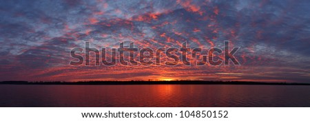 Panoramic view of the Olt river at dusk. The cloud cover turns crimson and reflects on the water surface (Romania, Olt County).