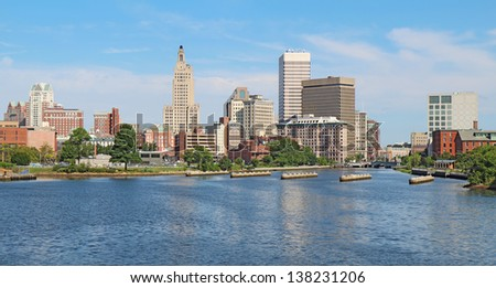 Panoramic view of the skyline of Providence, Rhode Island, from the far side of the Providence River against a blue sky and white clouds - stock photo