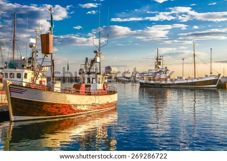 Panoramic view of traditional old wooden fisherman boats lying in harbor in beautiful golden evening light at sunset, town of Husavik, Skjalfandi Bay, Iceland, northern Europe - stock photo