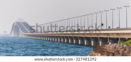 Panoramic view of traffic crossing the highest point of the King Fahd Causeway bridge between Saudi Arabia and Bahrain seen from the Causeway Island looking towards Saudi Arabia. - stock photo