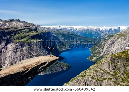 Panoramic view of Trolltunga, Odda, Norway. Sunny day with amazing blue sky. Majestic mountains in the background. Clear blue water. Scandinavian wilderness with standing man on the cliff rock.