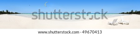 Panoramic view of tropical beach destination with plastic chairs - stock photo