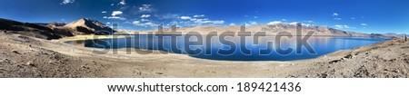 panoramic view of Tso Moriri lake, Korzok village and mounts Chamser Kangri and Lungser Kangri - Rupshu valley - Ladakh - India - stock photo