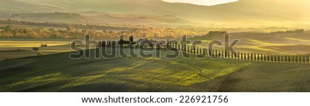 Panoramic view of Tuscan house with cypress trees along the road - stock photo