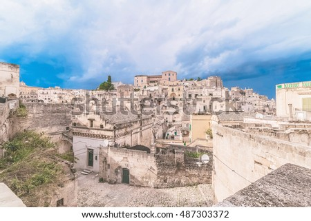 panoramic view of typical stones (Sassi di Matera) and church of Matera under blue sky, artistic style. Matera in Italy UNESCO European Capital of Culture 2019