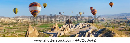 Panoramic view of unusual rocky landscape in Cappadocia, Turkey. Hot air ballooning in morning is most amazing attraction in Kapadokya. - stock photo