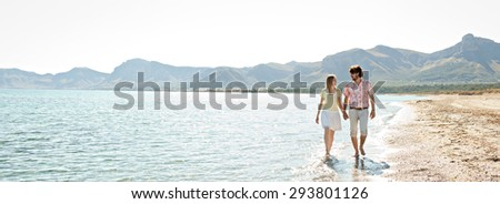 Panoramic view of young couple walking on the shore of a sandy beach with mountains, on a romantic holiday, outdoors. Travel tourists lifestyle. Couple enjoying recreational time together, exterior. - stock photo