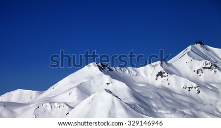 Panoramic view on snowy winter mountains and clear blue sky in sun day. Caucasus Mountains, Georgia, ski resort Gudauri. - stock photo