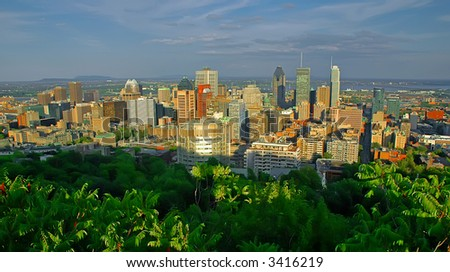Panoramic view over the skyline of Montreal (Quebec, Canada) at sunset. It is taken from a viewpoint on the Mont Royal. The foreground is dominated by green trees. - stock photo