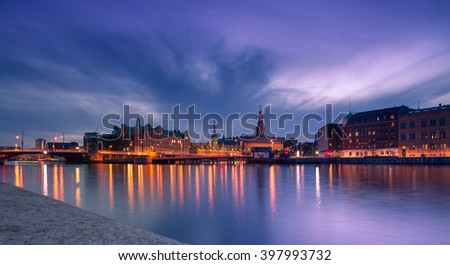 Panoramic view to Copenhagen city center and illuminated famous Stock exchange building at night with beautiful cloudy sky