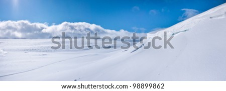 Panoramic view with a lonesome skier in a valley at easter in the norwegian mountains - stock photo