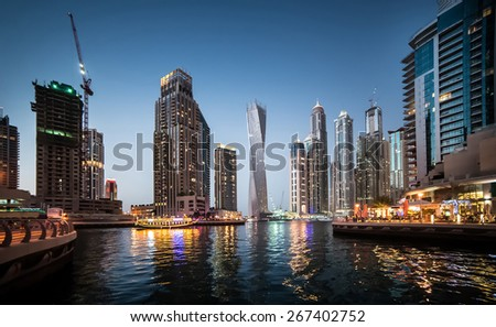 Panoramic view with modern skyscrapers and water channel of Dubai Marina in evening, United Arab Emirates - stock photo