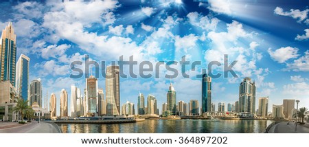 Panoramic view with modern skyscrapers and water pier of Dubai Marina at sunset, UAE.