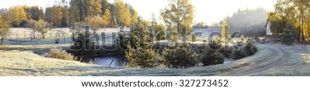 Panoramic views of the Early Autumn with White frost covered tree branches and leaves on frozen pond, the first rays of the morning sun and a new house, Latvia, the first snow - stock photo