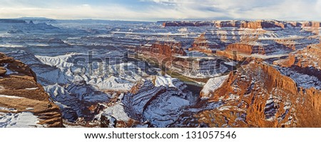 Panoramic wintry view of a gooseneck bend in the Colorado River and Canyonlands National Park from Dead Horse Point Overlook in Utah. - stock photo