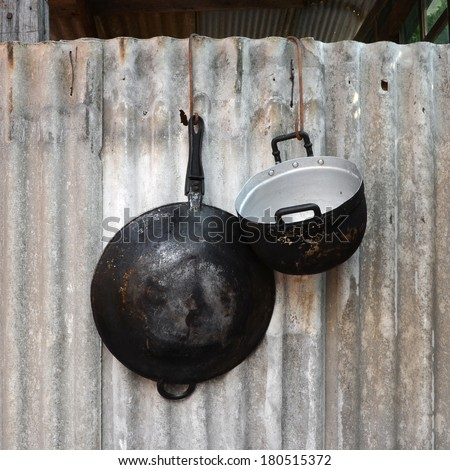 Pans and pots, old black and hung on the wall. - stock photo