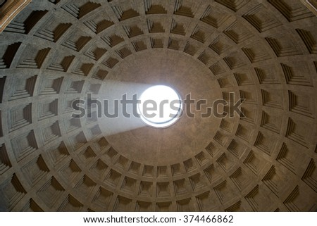 Pantheon dome as seen from inside the Pantheon with a visible light beam coming through the oculus, or open hole.  The dome is nearly 2000 years old and the world's largest unreinforced concrete dome. - stock photo
