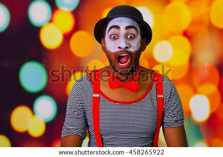 Pantomime man wearing facial paint posing for camera interacting making funny expressions, blurry lights background