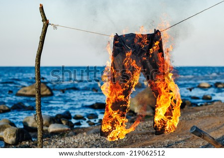 Pants burning on a rope on a seashore - stock photo
