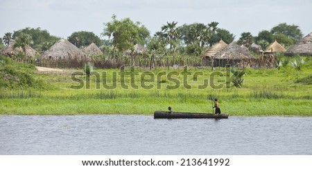 PANWEL, SOUTH SUDAN- JUNE 23 2012: Unidentified children canoe past their village on the Nile in South Sudan - stock photo