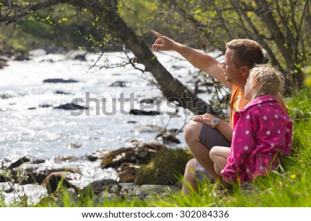 papa with daughter sitting on the shore of a mountain river, Norway - stock photo