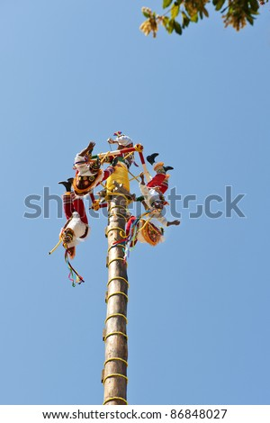 Papantla Flying Men in a clear blue sky of Xcaret Park Cancun, Mexico ancient Mayan Village on July 19, 2011 in Xcaret, Riviera Maya, Mexico - stock photo