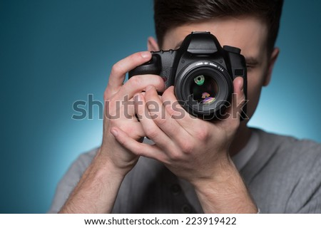 Paparazzi man taking picture with photo camera. Male photographer taking photos on blue background