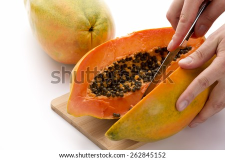 Papaya cut in half along the longitudinal axis of its oblong shape. A chefs right hand is guiding a kitchen knife, while his left is keeping the fruit in place. Cutout on white background. Close up. - stock photo