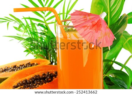 papaya fruit and glass of juice and exotic leaves - stock photo