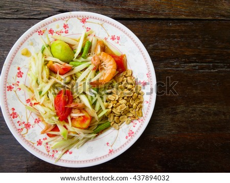 papaya salad in white plate on wooden background