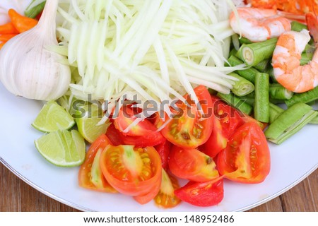 Papaya salad ingredients on wood background