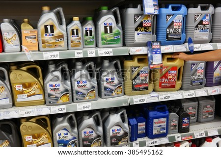 PAPENBURG, GERMANY - AUGUST 11, 2015: Automobile Motor Oil on a Supermarket aisle of a Real hypermarket. Engine oil is used for lubrication of various internal combustion engines. - stock photo