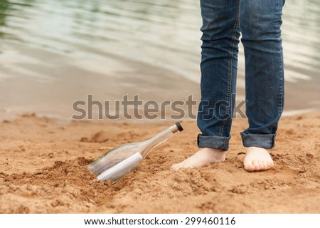 Paper a note in a bottle on the sand in the summer - stock photo