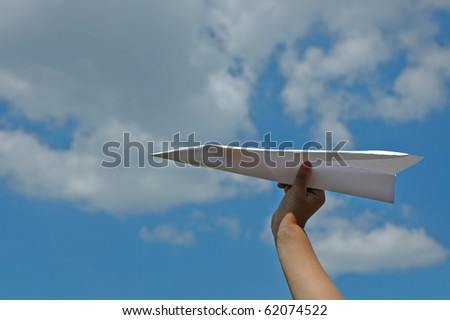 Paper airplane in child's hand on blue sky