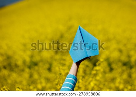 Paper airplane in children hands on yellow background - stock photo