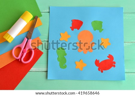 Paper applique with sea animals and fishes. Art lesson in kindergarten. Paper sea animals - octopus, fish, starfish, seahorse, crab. Kids crafts. Sheets of colored paper, scissors, glue  - stock photo