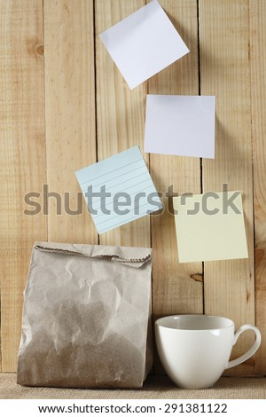 paper bag of some food and coffee cup and note pad paper or note paper on wooden background. breakfast time with planing.   - stock photo