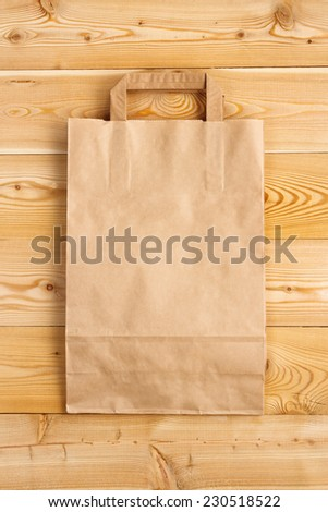 Paper bag on a wooden background - stock photo