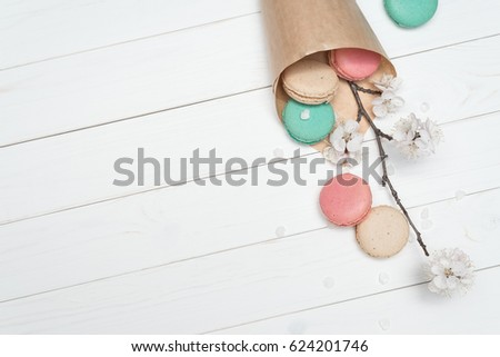 Paper bags with biscuits macaroon different colors. Delicious French dessert on a white wooden background. Branche with the flowers of apricot tree. Template for design. Flat layout, top view