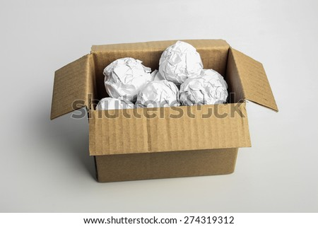 Paper balls are in the brown box on white background. - stock photo