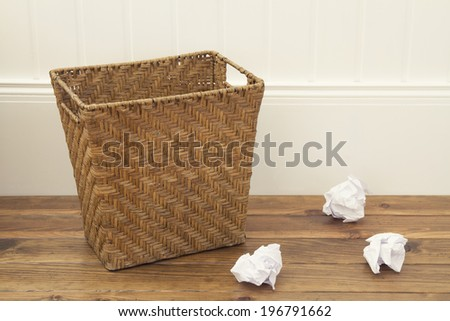 Paper bin and some balls of paper on the floor - stock photo
