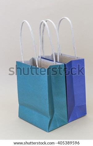 Paper blue and green shopping bag isolated on brown background - stock photo