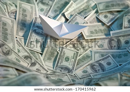 Paper boat at sea of money / studio photography of american moneys of hundred dollar on background  - stock photo